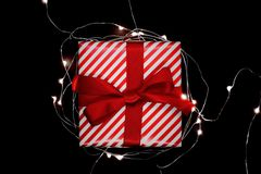 Christmas gift box with red ribbon encircled with illuminated ga. Rland and isolated on black background royalty free stock photos