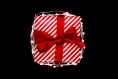 Christmas gift box with red ribbon encircled with illuminated garland and isolated on black background.  stock image