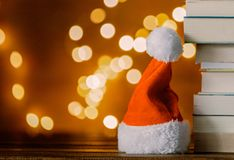 Christmas gift box, Santa Claus hat and pile of books royalty free stock photography