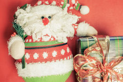 Christmas gift box with Santa Claus toy at red background Royalty Free Stock Image