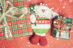 Christmas gift box with Santa Claus toy at red background Royalty Free Stock Photos