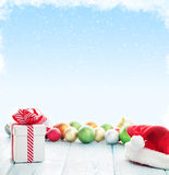 Christmas gift box, santa hat and colorful baubles Stock Photo