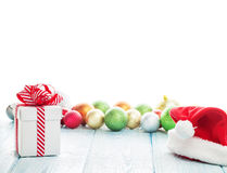 Christmas gift box, santa hat and colorful baubles Royalty Free Stock Photo