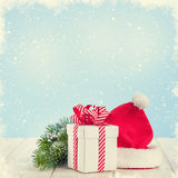 Christmas gift box, santa hat and tree branch Stock Photos