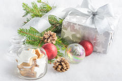 Christmas gift box in silver wrapping paper  over a white fluffy background. A jar full of star cookies and christmas decoration. Royalty Free Stock Photography