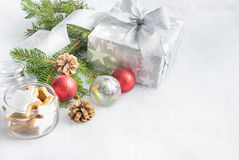 Christmas gift box in silver wrapping paper  over a white fluffy background. A jar full of star cookies and christmas decoration. Stock Photo