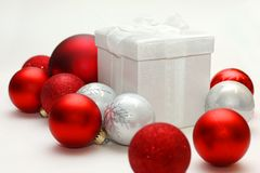 Christmas Gift Box Sitting Isolated with Red and Silver Ornament Royalty Free Stock Photos