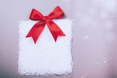 Christmas gift box in snow with red ribbon Stock Images