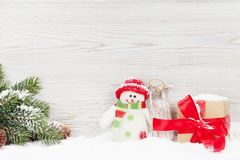 Christmas gift box, snowman toy and fir tree branch. View with copy space Royalty Free Stock Photos