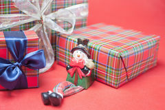 Christmas gift box with snowman toy at red background Royalty Free Stock Photo