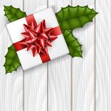 Christmas gift box from top view with red ribbon and green holly leaf. Realistic vector illustration for December holiday season, on white wood texture Stock Photography