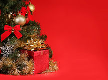 Christmas. Gift Box under Christmas Tree over Red Background Stock Images