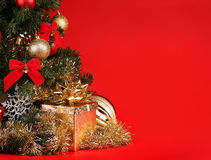 Christmas. Gift Box under Christmas Tree over Red Background Stock Photos