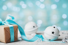Christmas gift box and white jingle bell against turquoise bokeh background. Holiday greeting card. Stock Photo