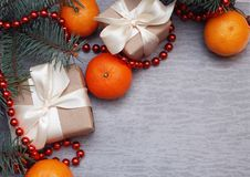 Christmas Gift Box with White Ribbon and Craft Paper. Cristmas Concept, Tangerine, fir Branches and Red Beads on Gray royalty free stock photos