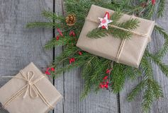 Christmas gift box on wooden table, handicraft wrapping, parchment, twine, fir tree twigs, cute simple last minute present handmad Royalty Free Stock Images