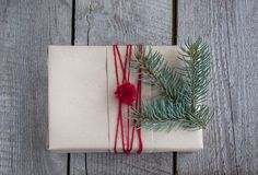 Christmas gift box on wooden table, handicraft wrapping, parchment, twine, fir tree twigs, cute simple last minute present handmad. E. Top view Royalty Free Stock Photos