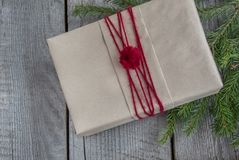 Christmas gift box on wooden table, handicraft wrapping, parchment, twine, fir tree twigs, cute simple last minute present handmad. E. Top view Royalty Free Stock Images