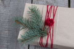 Christmas gift box on wooden table, handicraft wrapping, parchment, twine, fir tree twigs, cute simple last minute present handmad. E. Top view Stock Photo