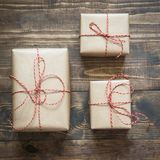 Christmas gift box wrapped in craft paper with decor around branch cypress on wooden surface. Square image Royalty Free Stock Images