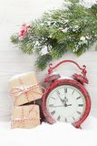 Christmas gift boxes, alarm clock and fir tree branch. Covered by snow in front of wooden wall Royalty Free Stock Photo