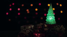Christmas gift boxes, ball and Christmas tree with blinking lights on bokeh light background.  stock footage