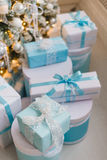 Christmas gift boxes with blue bow and bokeh lights on wooden surface. Christmas gift box with blue bow and bokeh lights on wooden surface Stock Image
