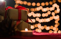 Christmas gift boxes and candle on red scarf with bokeh light background.  Stock Photo