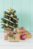 Christmas gift boxes and christmas tree. A christmas tree and some paper parcels wrapped tied with tags. A red heart and some christmas gift boxes wrapped with Royalty Free Stock Photo