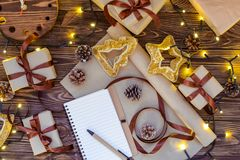 Christmas gift boxes in craft paper wjth satin ribbon, holiday decorations, notebook for planning, lights garland on dark wooden r. Ustic table. Christmas Royalty Free Stock Photography