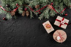 Christmas gift boxes on dark holiday background with Fir branches, pine cones, red decoration. Xmas and Happy New Year theme. Flat lay, top view, space for royalty free stock images