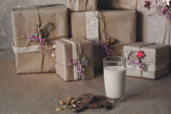 Christmas gift boxes decorated with lace and stars next to a glass of milk and cookies, lifestyle, holiday, gift, celebrate, greet Royalty Free Stock Image