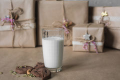 Christmas gift boxes decorated with lace and stars next to a glass of milk and cookies, lifestyle, holiday, gift, celebrate, greet Stock Image