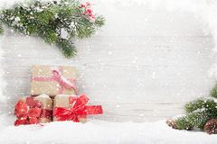 Christmas gift boxes and fir tree branch. Covered by snow in front of wooden wall. View with copy space Royalty Free Stock Image