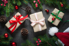 Christmas gift boxes. And fir tree branch at dark slate table. Handmade Royalty Free Stock Images