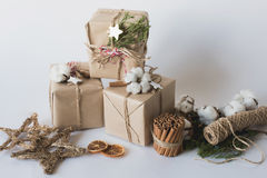 Christmas gift boxes with flowers and decorative objects Eco cotton, cinnamon, spruce branches and jute rope hank over white backg Royalty Free Stock Photography