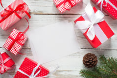 Christmas gift boxes and greeting card. Christmas card  and gift boxes at white wooden table. Flat lay Royalty Free Stock Photo