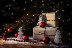 Christmas gift boxes in kraft paper decorated with red baubles,. Fir branches and small wooden trees, some snow and bokeh lights, dark rustic background with Royalty Free Stock Image