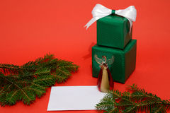 Christmas gift boxes and letter on the red background Royalty Free Stock Photos