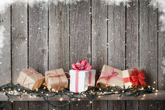 Christmas gift boxes and lights in front of wooden wall stock images
