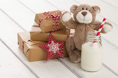 Christmas gift boxes and milk for Santa. A teddy bear, a red star and a school milk bottle with a straw on a white wooden table. some paper parcels &#x28 Royalty Free Stock Photo