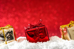 Christmas gift boxes ornaments on snow and red glitter background Stock Photography