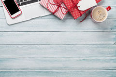 Christmas gift boxes, pc and coffee cup on wood Royalty Free Stock Images
