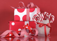 Christmas gift boxes on red background, with stripe candy canes. Stock Photos