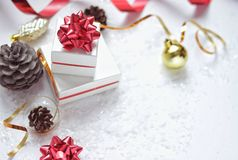 Christmas gift boxes with a red bow, next to the Christmas ball, red ribbon, cones on a white background with snow stock photography