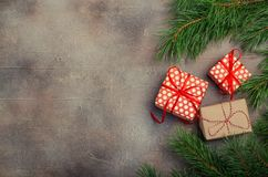 Christmas gift boxes with red ribbon on dark background with Fir branches. Xmas and Happy New Year composition. Flat lay Royalty Free Stock Photos