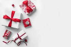 Christmas gift boxes with red ribbon and decoration on white background. Xmas and Happy New Year theme, snow. Flat lay, top view, wide composition royalty free stock images