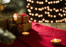 Christmas gift boxes on red scarf and candle on bokeh lights background.  Royalty Free Stock Images