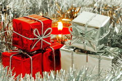 Christmas gift boxes, silver tinsel and candle flame Royalty Free Stock Photography