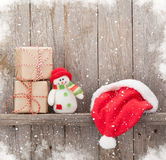 Christmas gift boxes, santa hat and snowman toy Royalty Free Stock Images